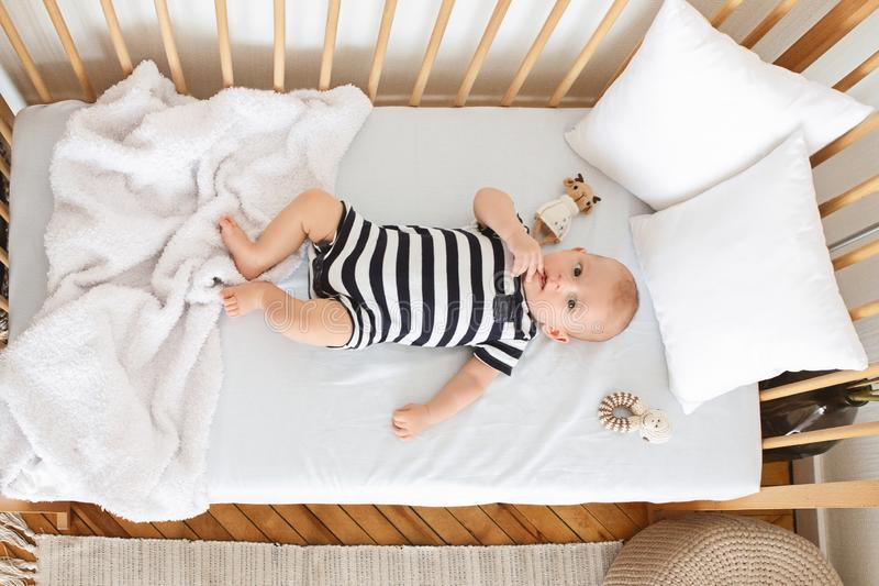 Curious infant baby lying in crib and chewing his finger stock images