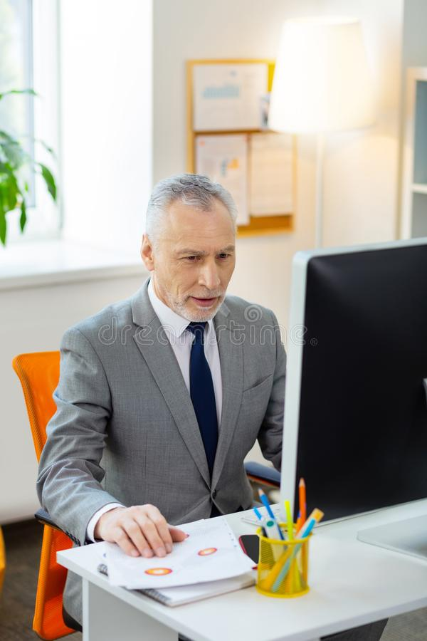 Curious involved grey-haired man in ironed costume. Senior worker deciding. Curious involved grey-haired man in ironed costume being concentrated on his main royalty free stock photos