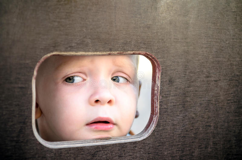 Curious kid spying through the hole in the wooden wall on playground royalty free stock photography