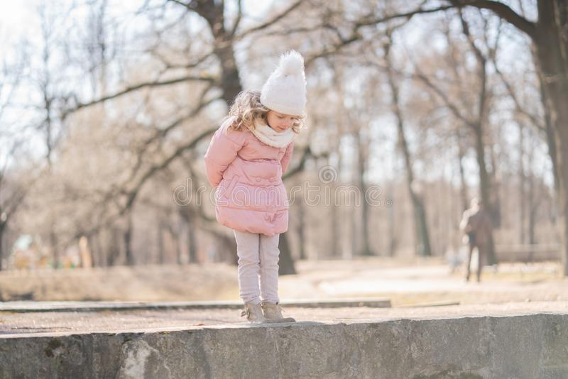 A curious little girl leaned over dangerously high alone. the concept of tracking, care children and their safety. stock photos