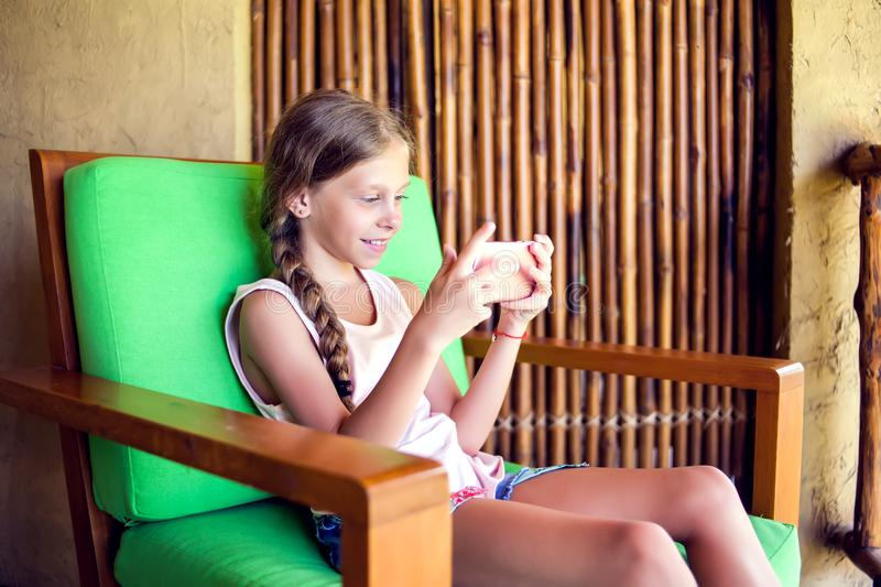 Curious little girl playing games on her mobile phone indoors. stock photo