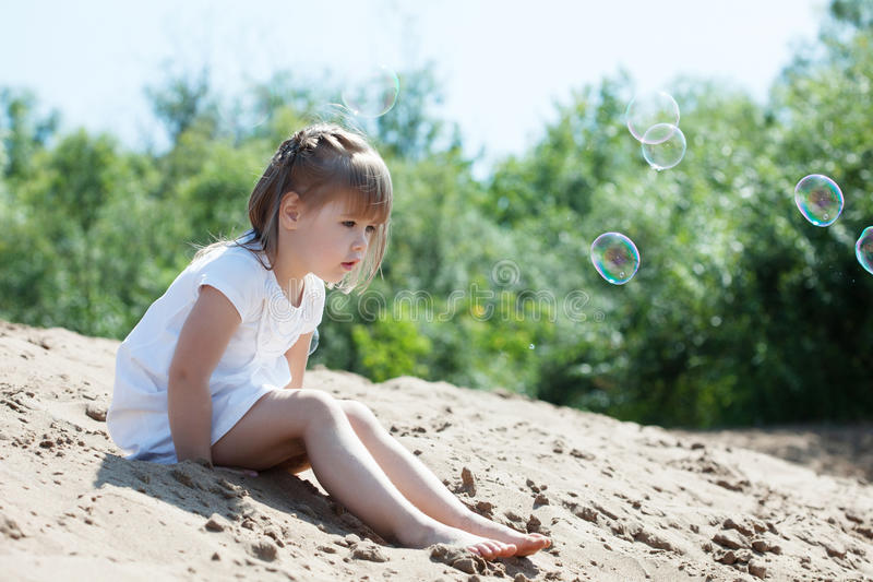 Curious little model sitting on sand in park. Image of curious little model sitting on sand in park stock photography