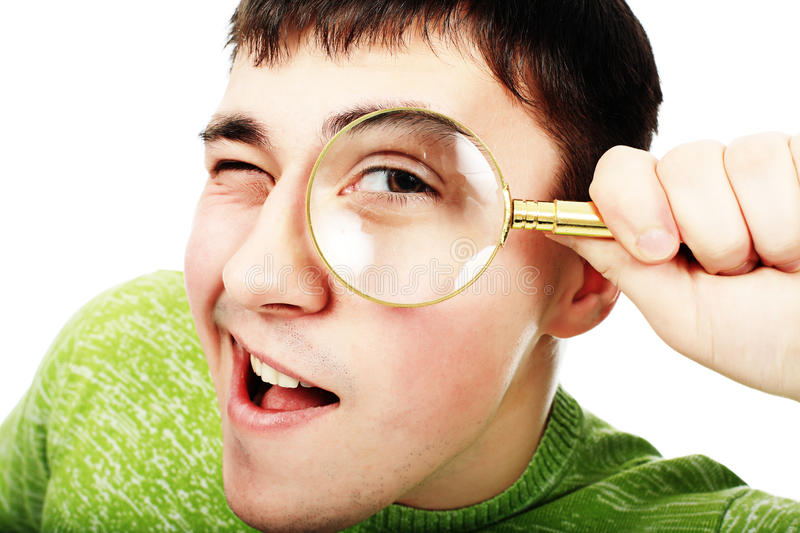 Curious man. Portrat of a young man looking through the magnifying glass stock image