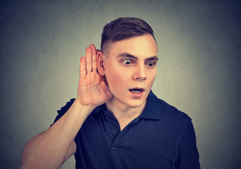 Curious young man eavesdropping with hand to ear gesture royalty free stock images