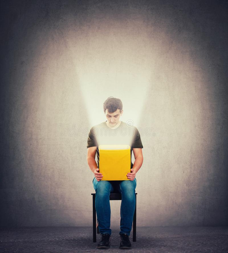Curious man sitting on a chair in a dark room holding yellow box on knees, looking inside as a magic light come out of the bin stock photos