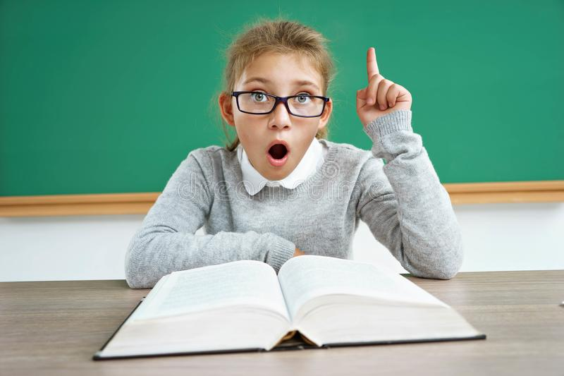 Curious schoolgirl reads a book. Did you know that?! Curious schoolgirl reads a book. Photo of astonished little girl wearing glasses pointing finger up royalty free stock images