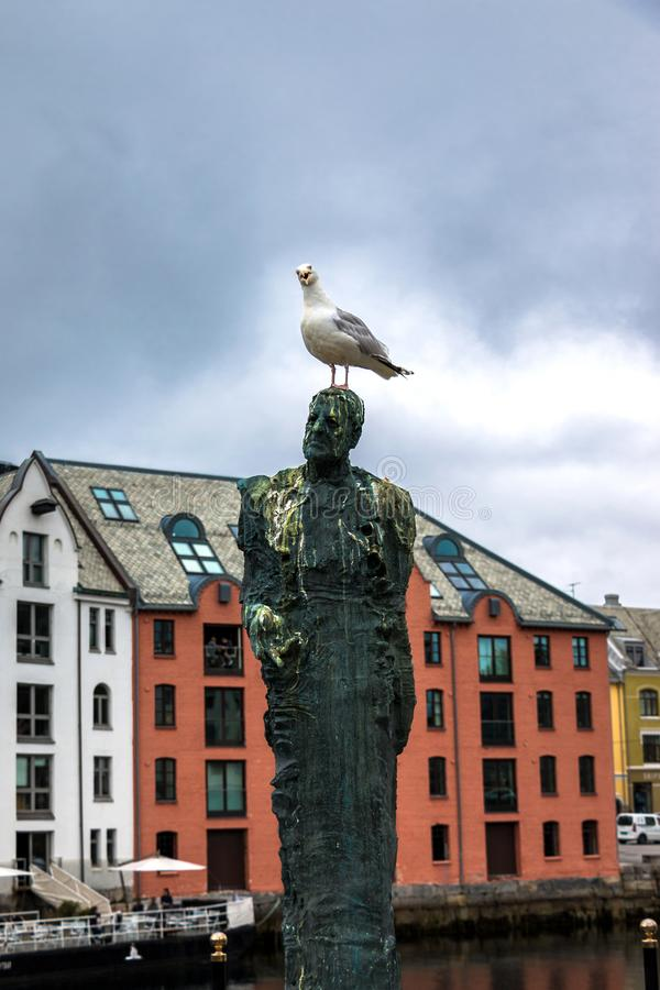 A Curious Seagull on The Head of A Man Statue royalty free stock image