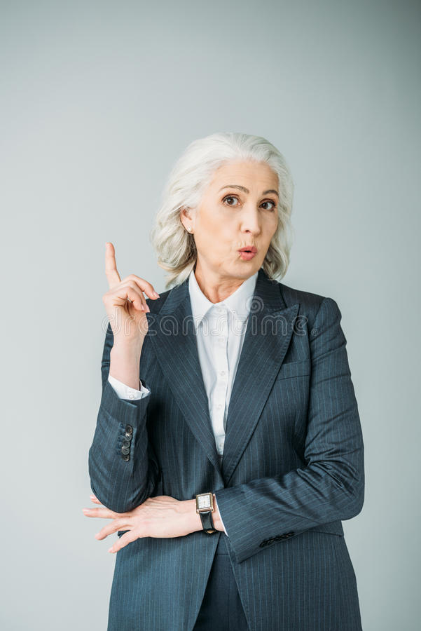 Curious senior businesswoman with arm up on grey. Portrait of curious senior businesswoman with arm up on grey royalty free stock photos