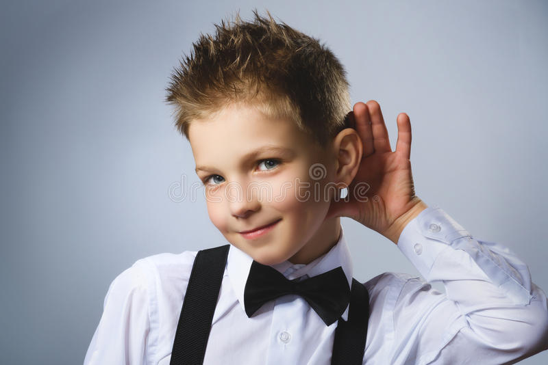 Curious smiling boy listens. Closeup portrait child hearing something, parents talk, hand to ear gesture isolated grey stock image