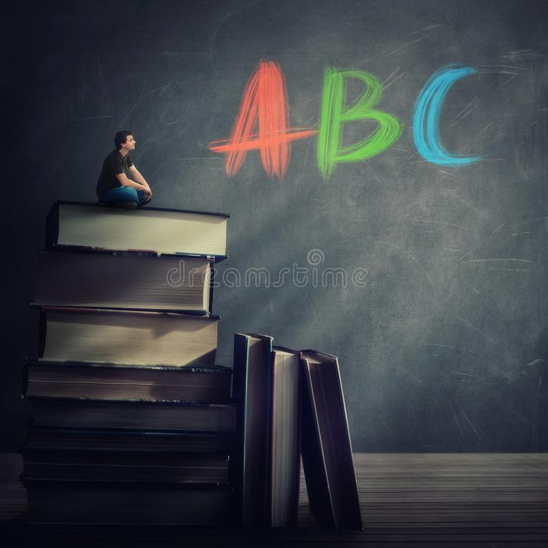 Curious student guy seated on the top of a huge atack of books looking at the blackboard with ABC letters written royalty free stock photo
