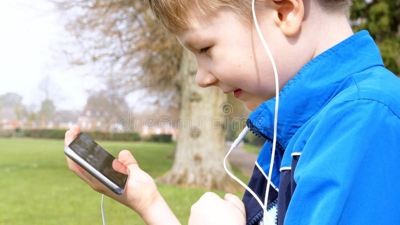 Curious teen boy with smart phone listening or talking while sitting in british park and biting his finger. teenager and. Social media concept royalty free stock photo