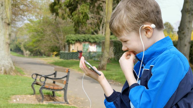 Curious teen boy with smart phone listening or talking while sitting in british park and biting his finger. teenager and. Social media concept royalty free stock photos