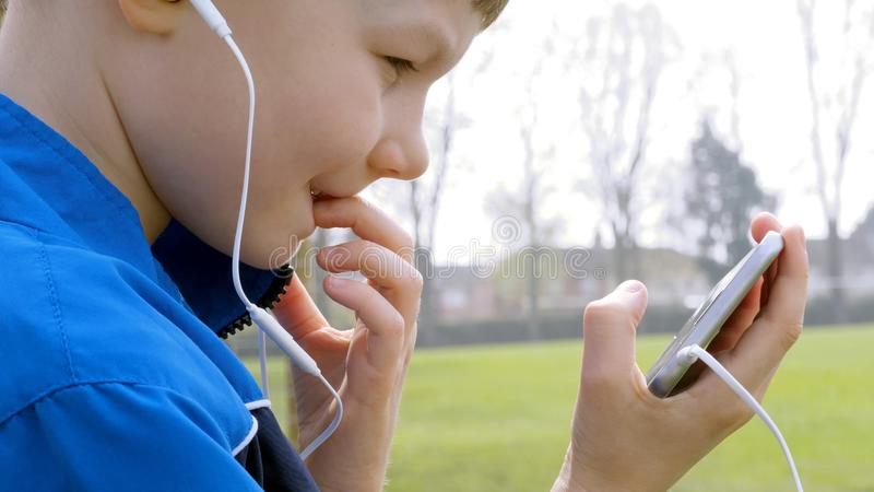 Curious teen boy with smart phone listening or talking while sitting in british park and biting his finger. teenager and. Social media concept royalty free stock photography
