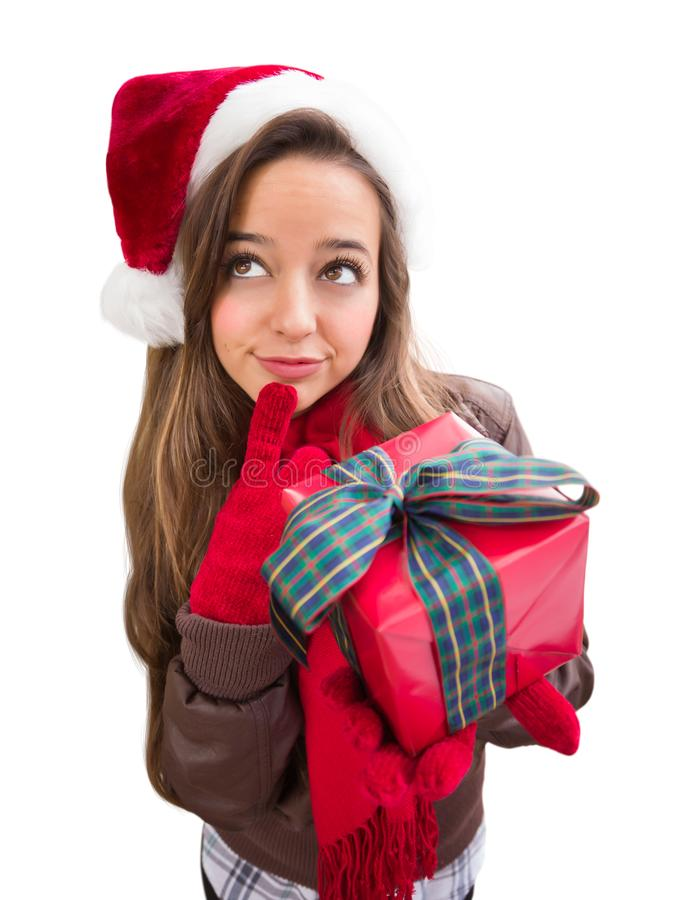 Curious Teen Girl Wearing A Christmas Santa Hat with Bow Wrapped Gif. Thinking Girl Wearing A Christmas Santa Hat with Bow Wrapped Gift Isolated on White royalty free stock photos