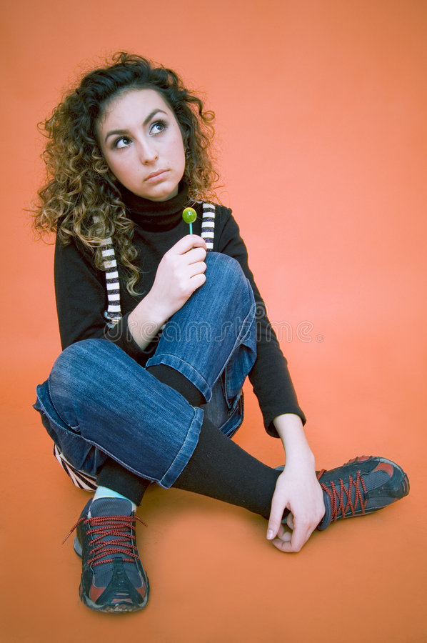 Curious Teen With A Lollipop. Teenage girl sitting with crossed legs, holding a green lollipop in her right hand, looking up with a raised eyebrow. Curious stock photos