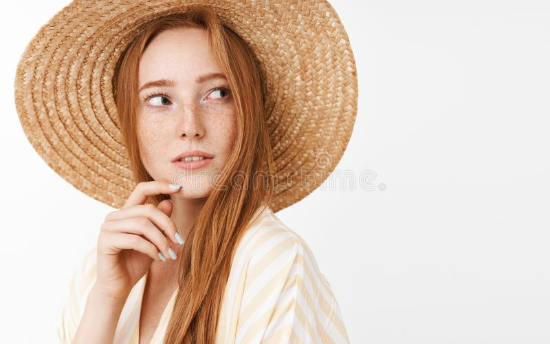 Curious thoughtful charming ginger girl with cute freckles in trendy summer straw hat turning right and gazing with stock photos