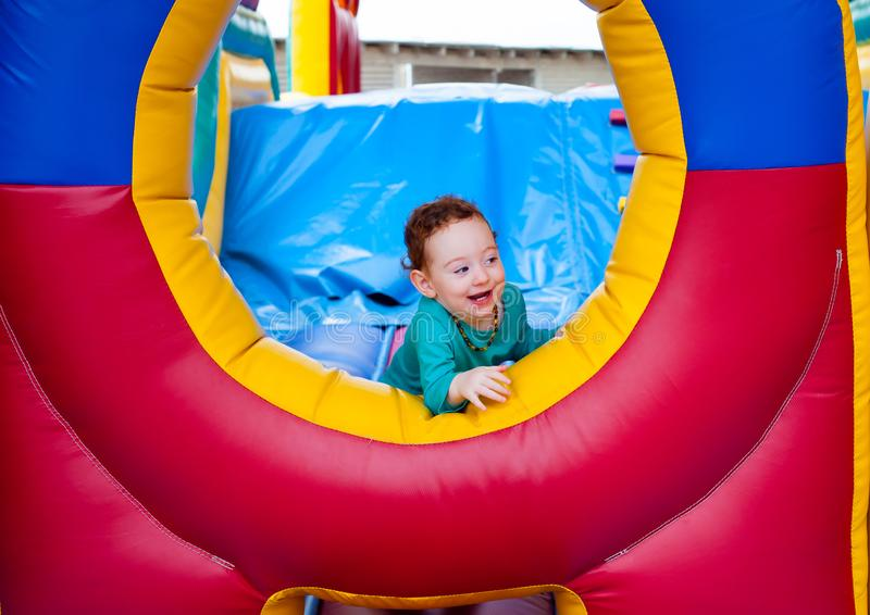 Curious toddler peeking out. Curious funny toddler peeking out from colorful trampoline castle stock photography