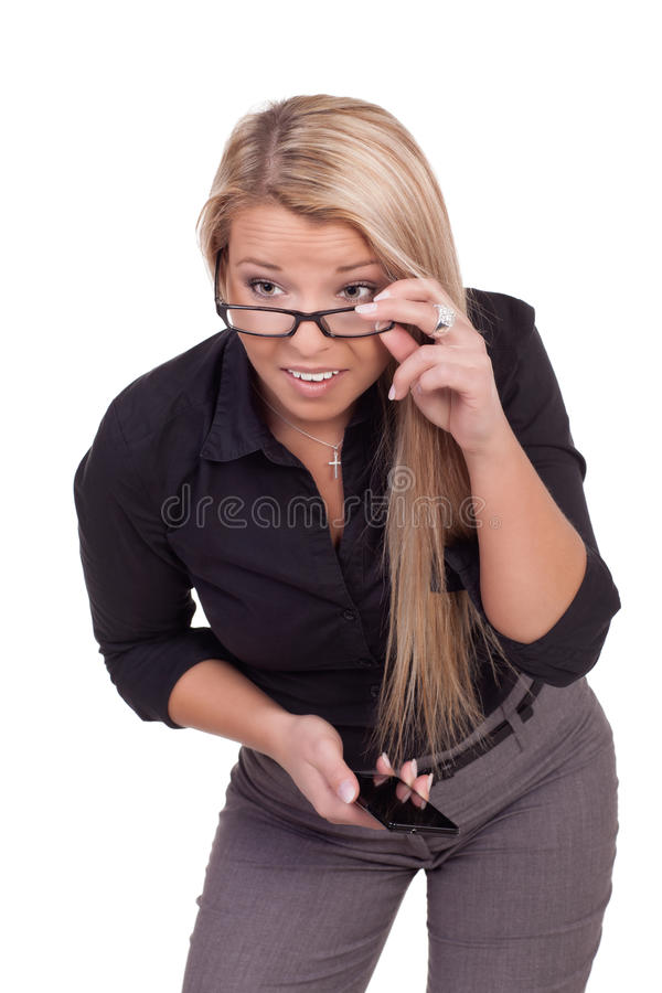 Curious woman bending forwards. Attractive young blonde woman in stylish clothes bending forwards curious to see what is happening and adjusting her glasses with stock photography