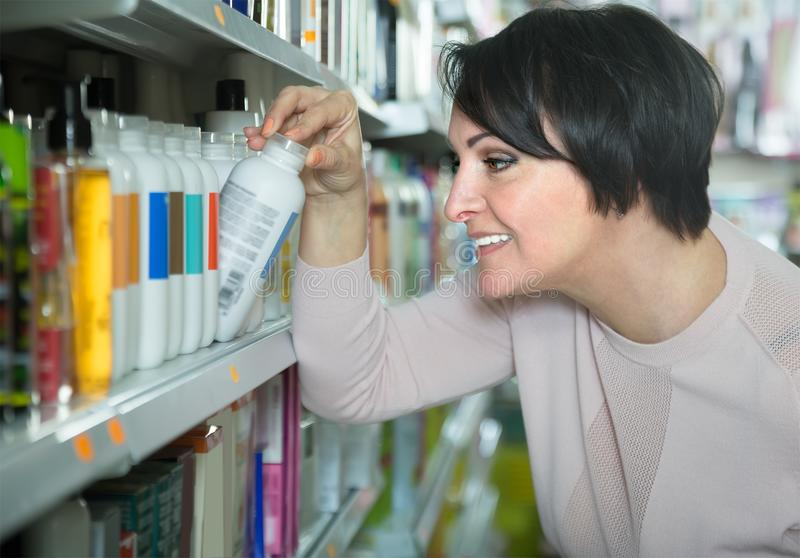 Curious woman choosing bottle of shampoo in supermarket stock photo