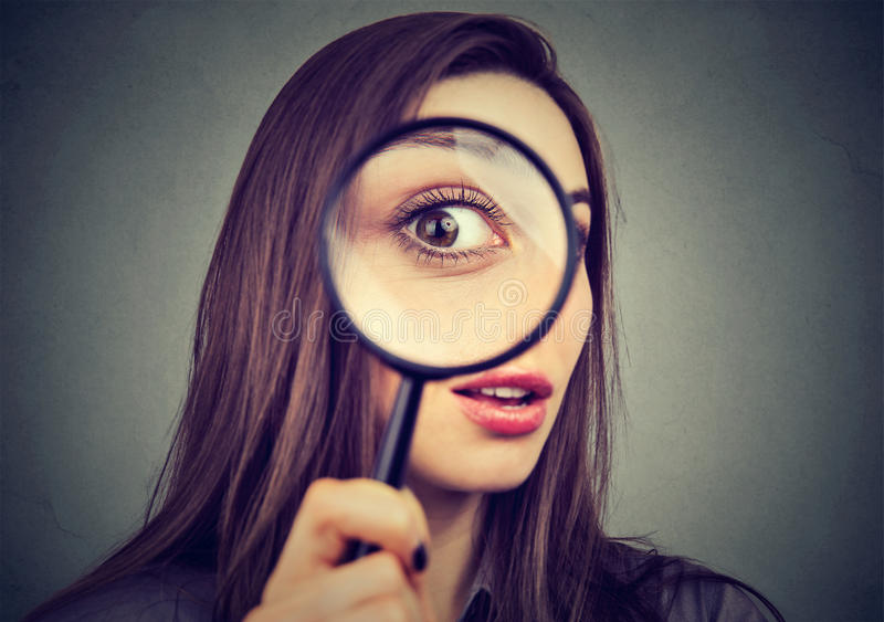 Curious woman looking through a magnifying glass stock image