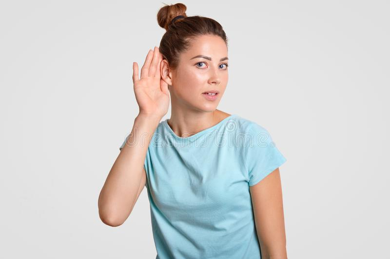 Curious woman puts hand near ear, tries to eavesdrop or overhear secret information, likes gossiping, dressed in casual blue t shi. Rt, isolated over white stock image