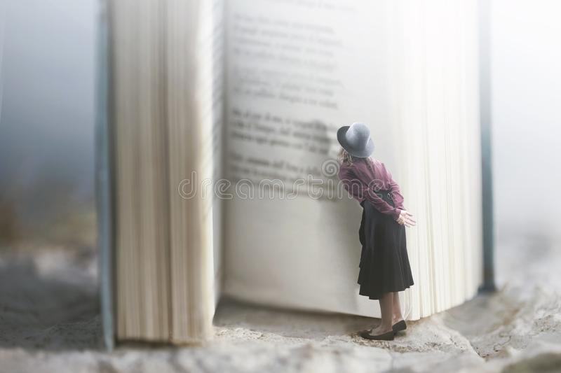 Curious woman reads a giant book royalty free stock photo
