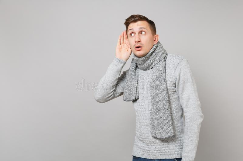 Curious young man in gray sweater, scarf eavesdrop, hearing with hand near ear on grey background. Healthy. Fashion lifestyle, people sincere emotions, cold royalty free stock images