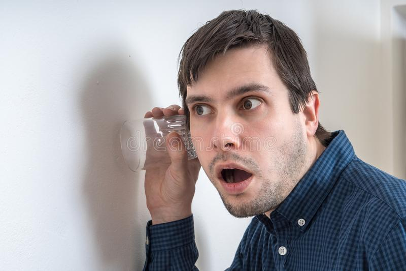 Curious young man is listening and spying on neighbours behind wall royalty free stock images