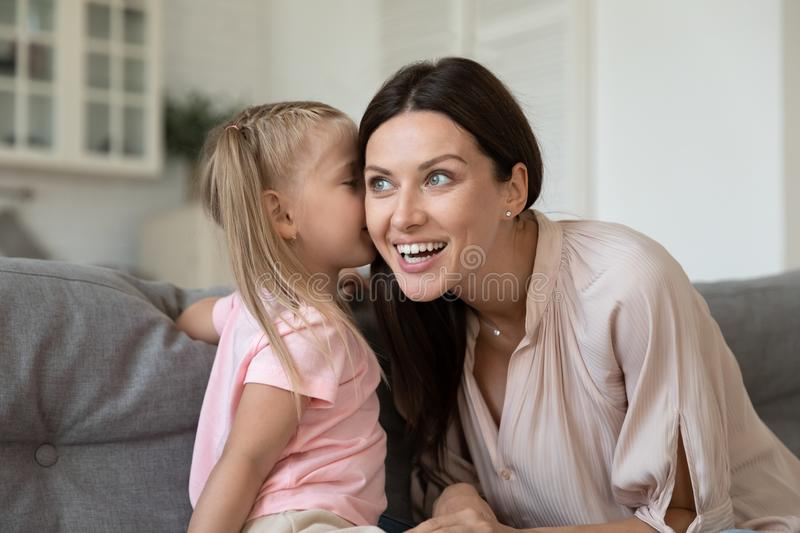 Curious young smiling woman listening attentively to little daughters secret. stock image