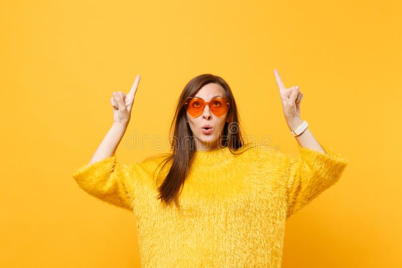 Curious young woman in fur sweater and heart orange glasses pointing index fingers up on copy space isolated on bright stock photography