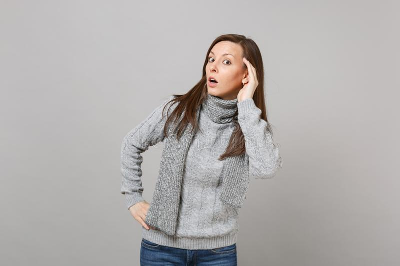 Curious young woman in gray sweater, scarf eavesdrop hearing gesture on grey background in studio. Healthy. Fashion lifestyle, people sincere emotions, cold stock photo