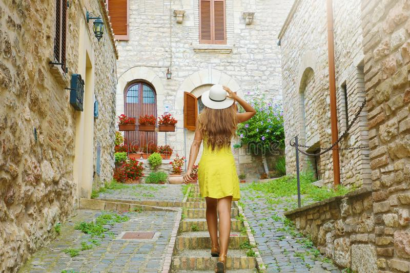 Curious young woman with yellow dress and hat goes upstairs in medieval street in Tuscany, Italy. Rear view of happy cheerful girl stock photography