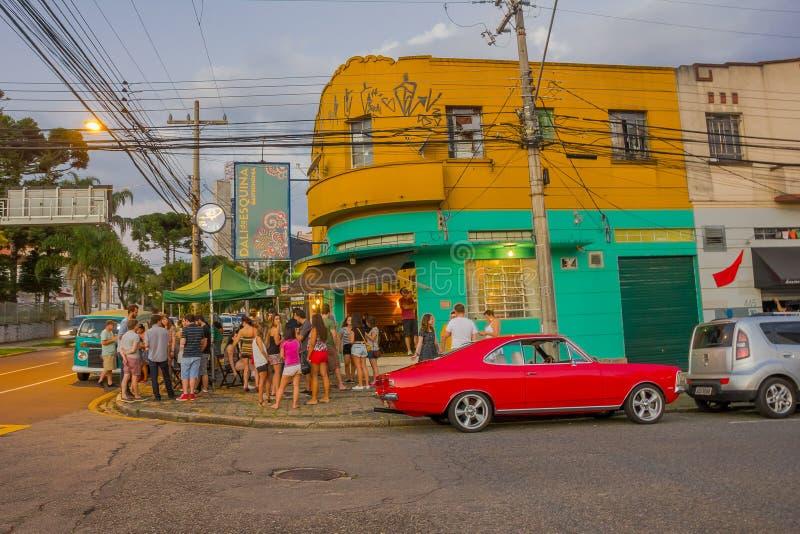CURITIBA, BRÉSIL - 12 MAI 2016 : la voiture classique rouge intéressante a garé à un coin où certains attendent en dehors d'a images libres de droits