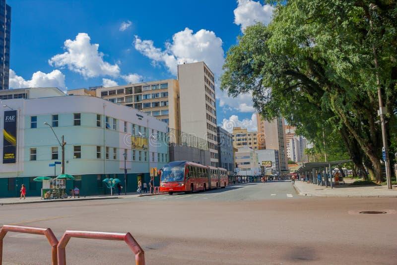 CURITIBA, BRÉSIL - 12 MAI 2016 : le grand autobus public rouge s'est garé dans un coin devant un parc attendant quelques piétons photographie stock libre de droits