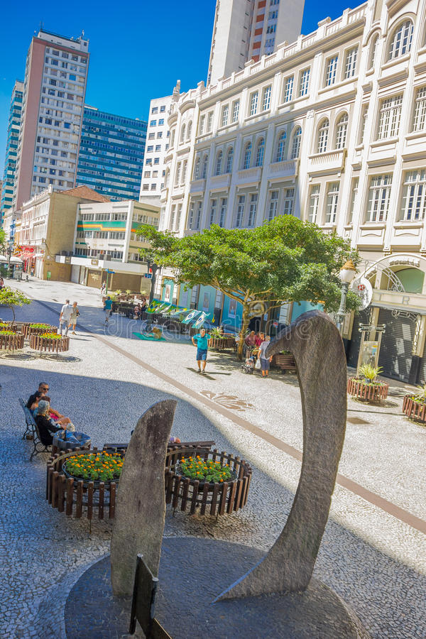 CURITIBA, BRASIL - 12 DE MAIO DE 2016: monumento de pedra situado em um bulevar, pessoa que senta-se em um banco na rua foto de stock