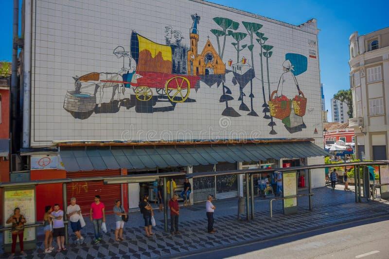 CURITIBA, BRASIL - 12 DE MAIO DE 2016: povos não identificados que esperam o ônibus em uma estação sob uma parede pintada fotografia de stock