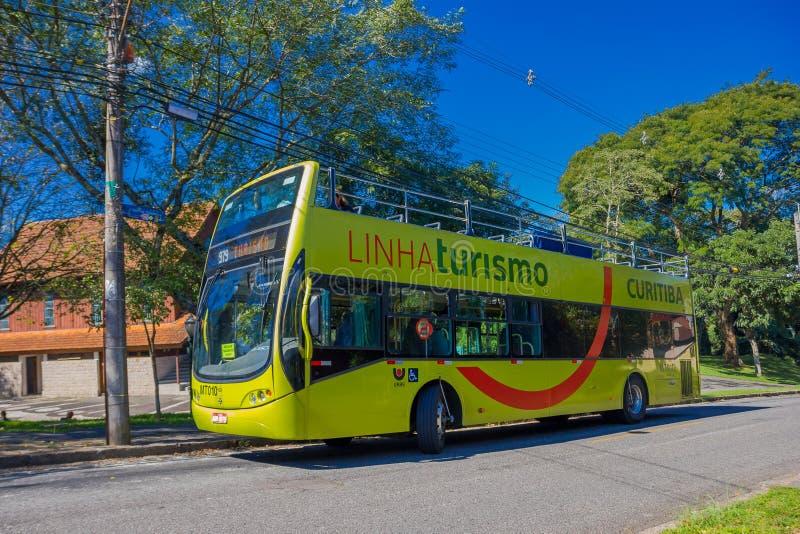 CURITIBA BRASILIEN - MAJ 12, 2016: den gröna bussen turnerar att vänta på stoppet som parkeras i gatan bredvid några träd arkivbild