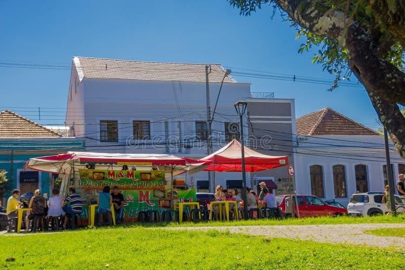 CURITIBA BRASILIEN - MAJ 12, 2016: några personer som utanför lite äter bredvid matställningen som erbjuder något som är traditio arkivbild