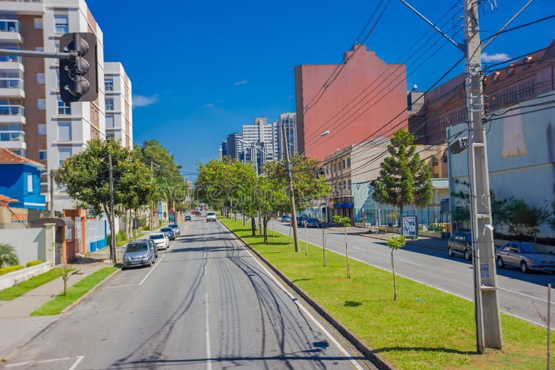 CURITIBA ,BRAZIL - MAY 12, 2016: long empty street with some autos parked at the sides and some trees on the sidewalk.  stock photos