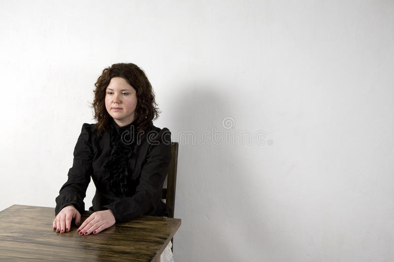 Curl smiling woman sitting at the table stock photo