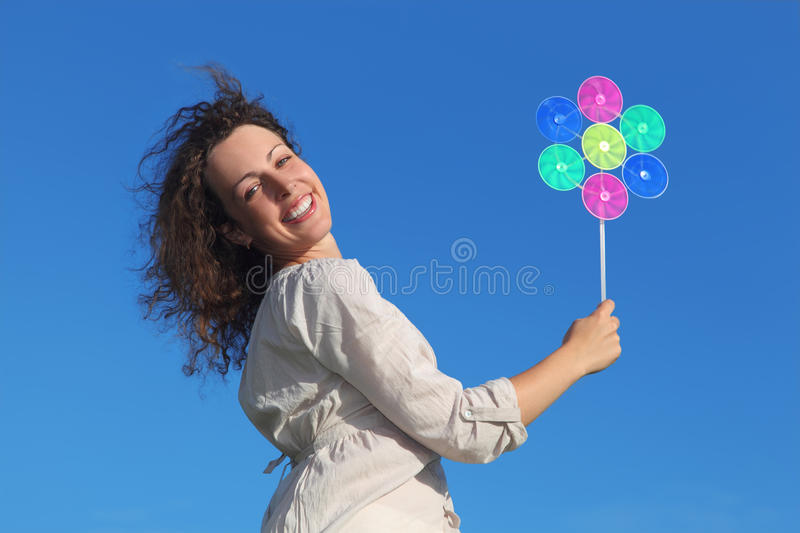 Curl woman holding pinwheel toy and smiling