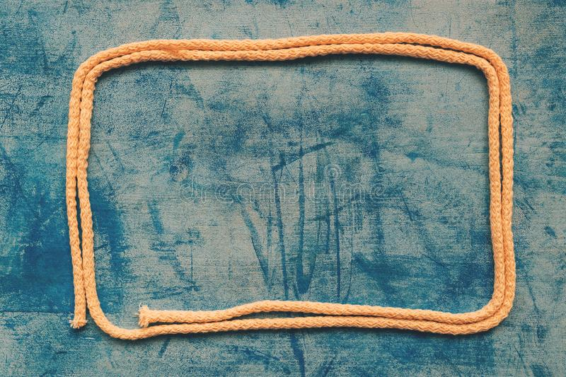 Curled rope as frame on wooden background royalty free stock photos
