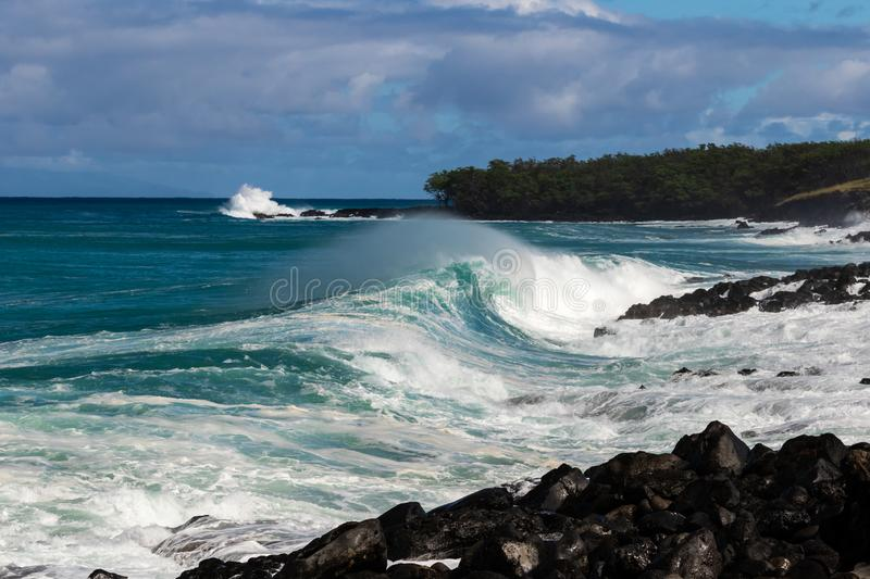 Curling wave trailing sea spray breaking near shore on Hawaiian cost. Strip of land in background with rocks and trees. Cloudy Sky royalty free stock photography