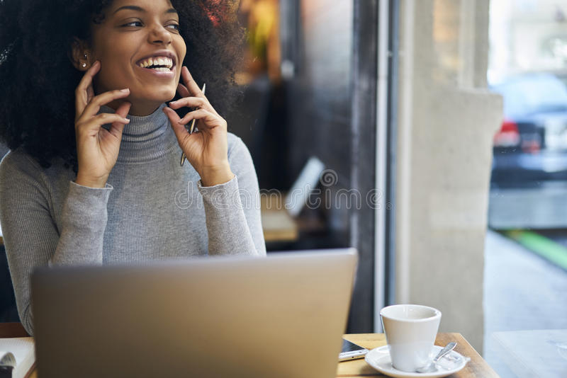 Curly African-American in a gray jacket using wireless connection to fast internet in cafe wifi zone royalty free stock image