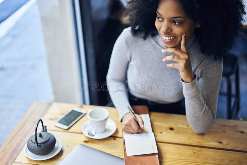 Curly African-American in a gray jacket writing her new detective novel for book house while drinking hot tea royalty free stock image