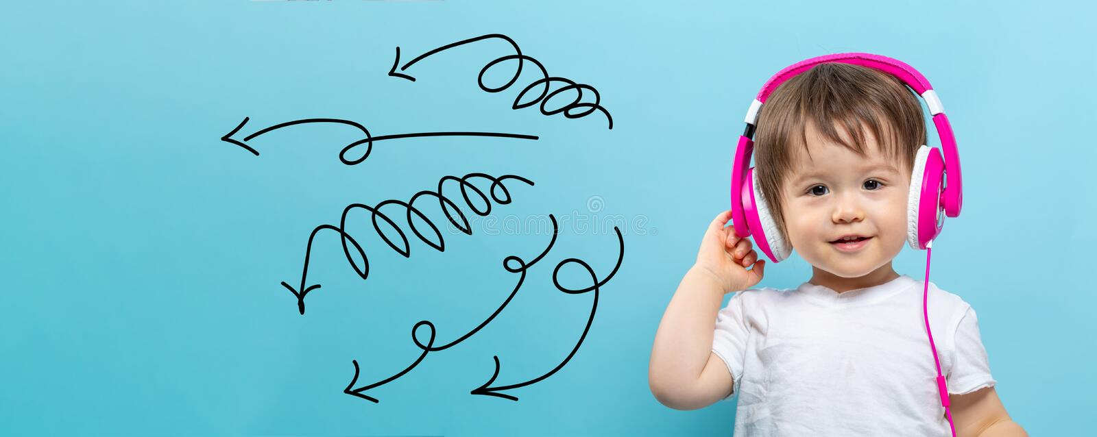Curly arrows with toddler boy with headphones royalty free stock photo