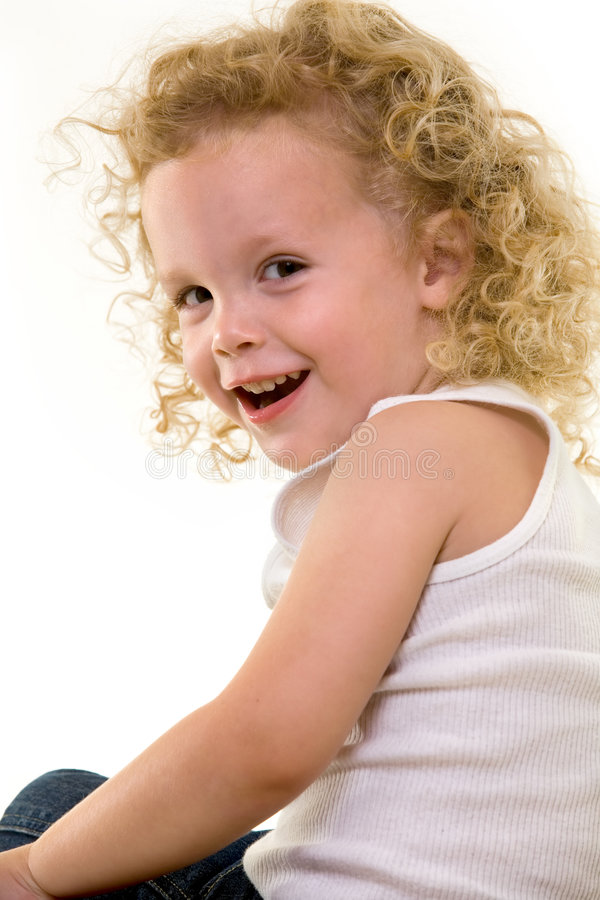 Curly blond hair. Portrait of an adorable little three year old boy wearing white top sitting on a chair with a curly long blond hair with a cute smile stock photo