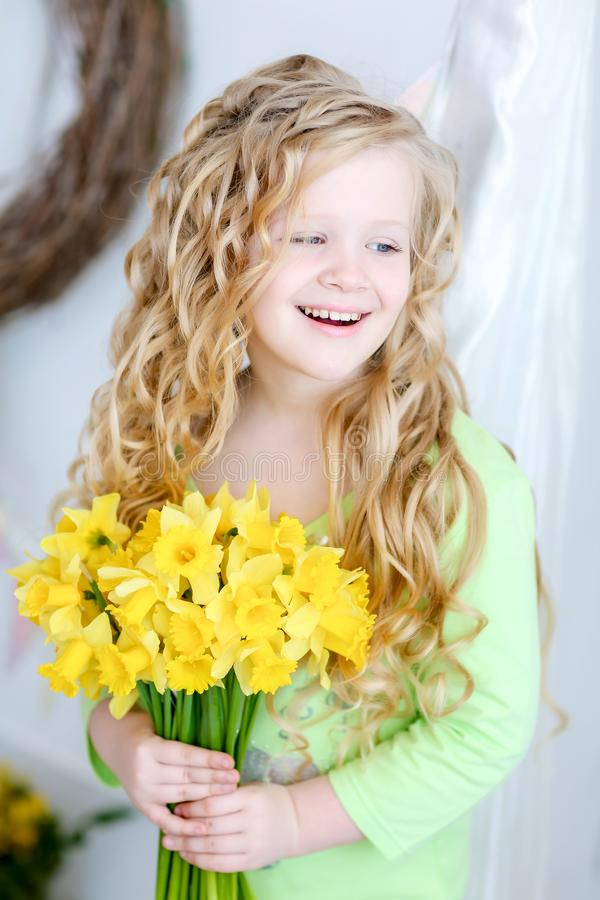 Curly blond-haired girl in the studio holding a bouquet of yellow flowers royalty free stock image