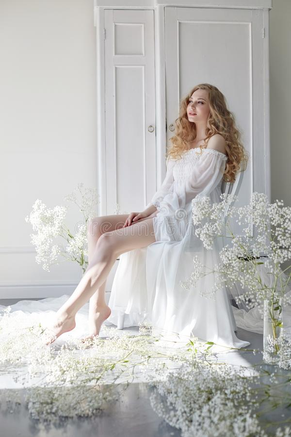 Curly blonde romantic look, beautiful eyes. White wildflowers in hands. Girl white light dress and curly hair, portrait of woman stock photo