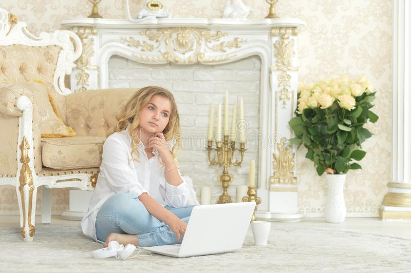 Curly blonde teenage girl in casual clothing sitting on floor stock photos